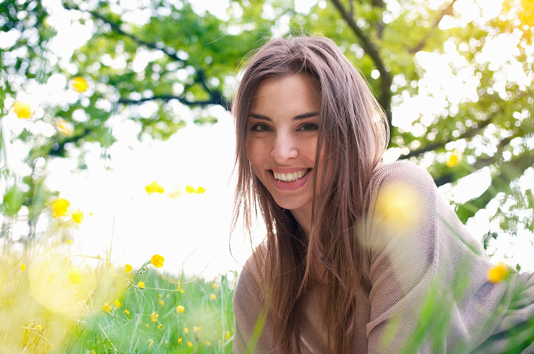 Donna con lenti a contatto adagiata sull'erba in una giornata soleggiata.