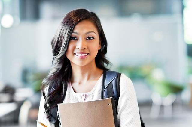 Una ragazza con le lenti a contatto che indossa una zaino e porta i suoi appunti