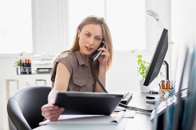 Una donna in ufficio con le lenti a contatto mentre telefona e guarda il tablet