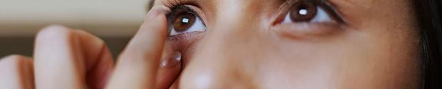 Una ragazza che guarda i suoi occhi allo specchio mentre si mette le lenti a contatto