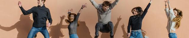 Un gruppo di amici che usa le lenti a contatto sospesi in aria in un salto con le mani alzate