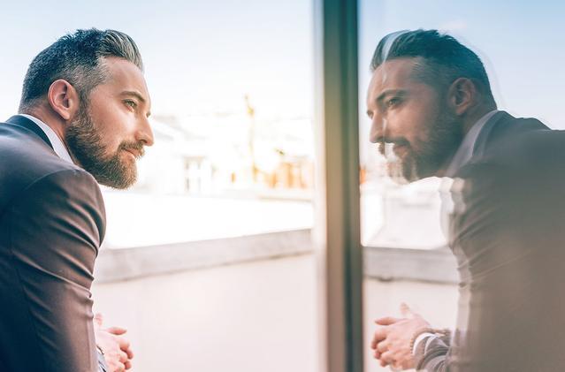 Immagine di un uomo adulto che guarda al suo riflesso nella finestra