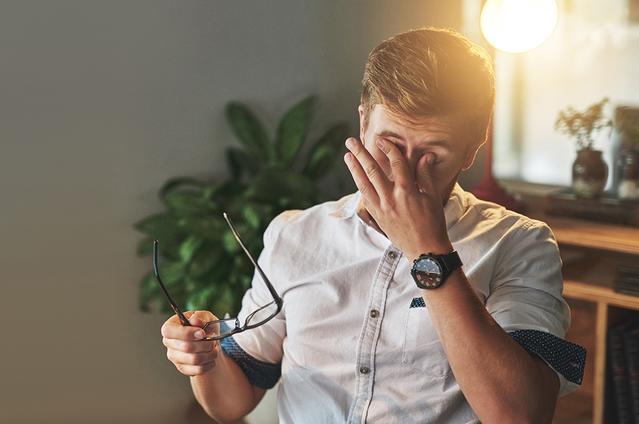 Immagine di un uomo che si toglie gli occhiali e si strizza gli occhi