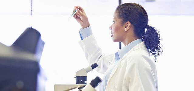 Una dottoressa in divisa mentre ispeziona una provetta