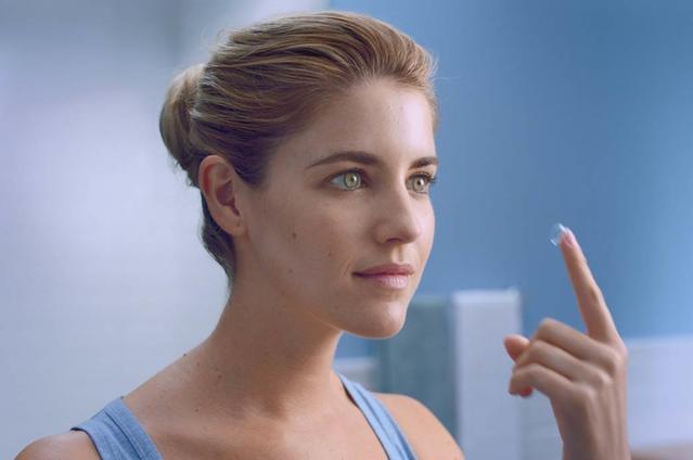 Una giovane donna guarda attraverso una macchina fotografica della retina dall'ottico
