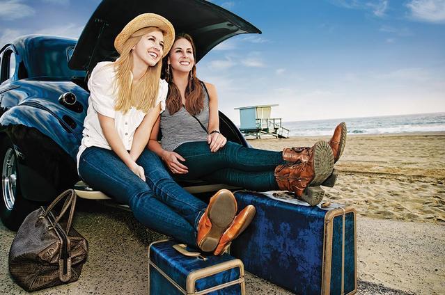 Due ragazze sedute sul bagagliaio dell'auto sulla spiaggia. Pronte con le loro valigie per andare in vacanza.