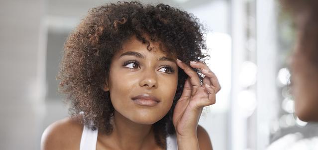 Una giovane donna mentre guarda i suoi occhi allo specchio