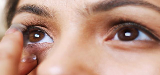 Vista ravvicinata di una giovane donna mentre si mette le lenti a contatto