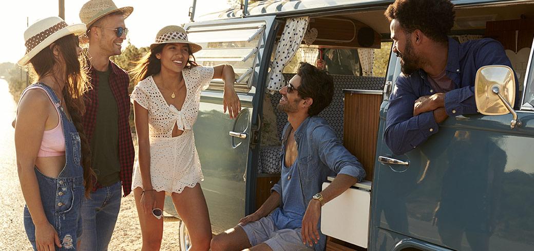 Un gruppo di amici che indossa le lenti a contatto si ritrova e ride insieme vicino al loro camioncino