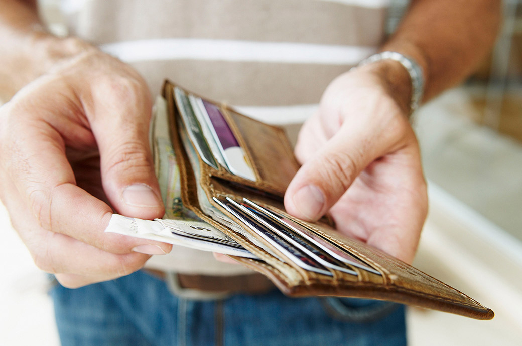 Una vista ravvicinata di qualcuno che prende delle banconote dal portafoglio