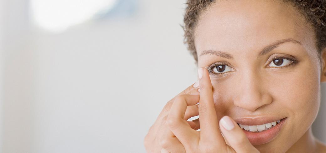Una donna tiene una lente a contatto sul suo ditto e si appresta ad indossarla